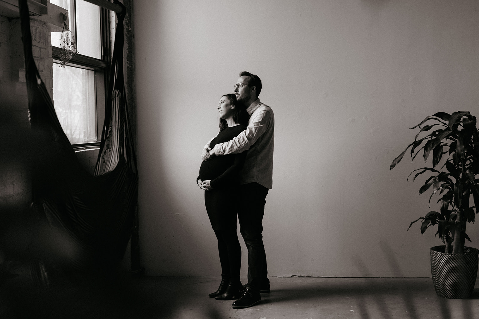 Montreal maternity session. Photographer takes photos of couple in-studio.