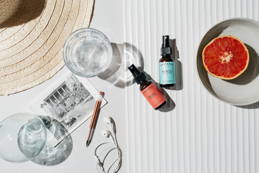 Skincare products on white background with glass and summer hat in photo. Picture taken by Montreal Photographer.